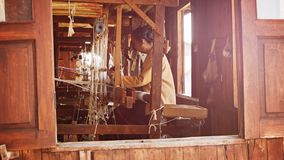 Old weaving factory. A local woman has been producing of fabric on a loom stock video