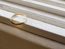 Only an old wedding ring, in gold. On a white dresser Royalty Free Stock Images