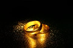 Old wedding rings, water effect. A shot of two gold wedding rings Stock Photos