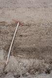 Old weeding tool or rake abandoned lying in garden on soil. Vert. Ical image royalty free stock photos