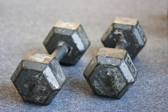 Old weights on carpet floor. Old 25-pound hand weights on carpet floor Royalty Free Stock Photo