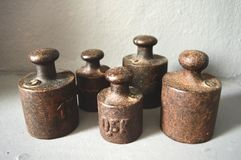 Old weights. Old metal weights, 0,5 and 1 kilo. Still life contains 5 pieces of weight and is on a gray background stock photos