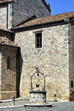 Old well. A stone well in a square in the town of San Quirico D'Orcia in Italy Stock Photo