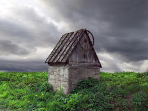 Old well. An old weathered well against dramatic sky background Stock Photo