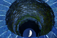 Old well. Light moon in an old well with blue tone Stock Images