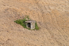 Old well made of stone in a ploughed field Piedmont Italy Stock Image