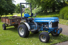 An old but well maintained Ford tractor and box trailer in use daily in the West Dean Estate gardens in Hampshire England. An old but well maintained Ford royalty free stock images