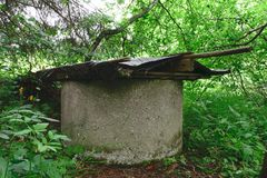 Old well in the middle of bushes and covered with lid stock image