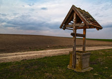 An old well. Near rural road at field Stock Images