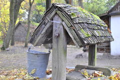 The Old well near the cottage with the metal bucket standing near by. royalty free stock photo