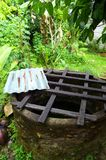 Old well with safety grid, farm house. A photograph showing an old stone well behind a chinese farmhouse in Malaysia.  Wooden grid to prevent anyone from falling Royalty Free Stock Image