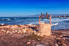 Old well on the seashore. Under blue sky Royalty Free Stock Photography