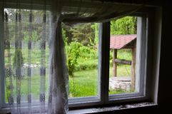 Old well seen through a rustic window. An old well in green garden seen through a rustic window of a retro house, with dirty curtains pulled aside stock images