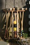 Old well-used Croquet Mallets in a rack leaning against a wooden wall royalty free stock photo