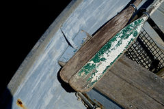 Old well used oars in a skiff. Old weathered and salt water used oars sit in a wooden skiff Royalty Free Stock Photography
