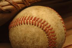 Old well-worn Baseball in a glove. Stock Photography