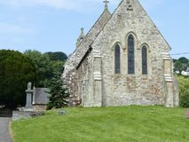 Old Welsh  church. A 15th century Welsh stone church with lush green grass and trees with blue sky Royalty Free Stock Photography