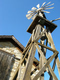 The Old West. Stark blue sky behind a rustic setting of a pioneer windmill and stone building Royalty Free Stock Photos