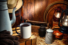 Old West Coffee Mug in Antique Western Chuck Wagon. Old American West enamel coffee mug and vintage pot with traditional working cowboy tools and ranching stock photography