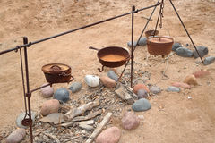 Old West Cooking Utensils. Old cast iron cooking utensils and metal framework to hold them over fire pit Stock Photos