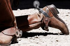 Old West Cowboy Boots & Spurs. Close-up of a pair of period-correct Old West cowboy boots and spurs on a cowboy kneeling during an Old West reenactment royalty free stock photo
