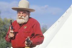 Old West gunslinger drawing guns. During historical reenactment, CA Stock Image