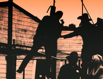 Old West-Outlaw Hangs. An outlaw hangs for his crimes in the Old West as the widow weeps Stock Photo