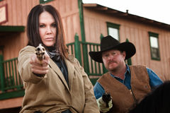 Old West Partners Aim Guns. Pretty women and partner aim guns in old west town Stock Photography