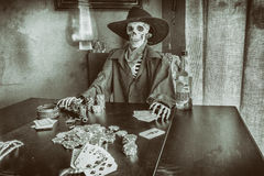 Old West Poker Playing Skeleton. Old west bandit outlaw skeleton at a poker table with a pistol and bourbon, edited in vintage film style stock photography