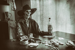 Old West Poker Skeleton. Old west bandit outlaw skeleton at a poker table with a pistol and bourbon, edited in vintage film style royalty free stock image