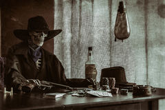 Old West Poker Skeleton Gun. Old west bandit outlaw skeleton at a poker table with a pistol and bourbon, edited in vintage film style stock images