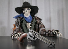 Old West Revolver Skeleton. Old west bandit outlaw skeleton at a poker table with a colt 45 pistol revolver, edited in vintage film style with shallow depth of royalty free stock photo