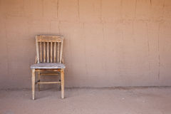 Old western chair against an adobe wall Stock Images