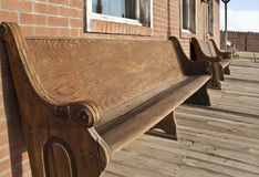 Old Western church pews outside bank. Old Western town church pews serve as seating outside bank Royalty Free Stock Photo