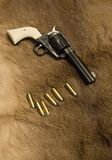 Old Western Revolver. Old Western style revolver with ammo on top of an old deer skin Royalty Free Stock Photography