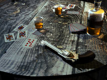 Old western saloon table. On a wooden table, in an old saloon, a gun, playing cards, two glasses and a bottle with some whisky stock illustration