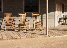 Old Western Town Rocking Chairs. Three rocking chairs sit empty on wooden sidewalk of an old western town royalty free stock photography
