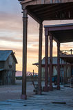 Old western town in rural New Mexico as the sun is setting. Rough hewn wooden buildings of an old western town stand in the light of the setting sun in rural Stock Image