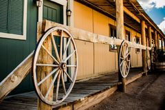 Old western village buildings with wooden wheels on the fence stock images