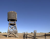 Old Western Water Tower. Wooden water tower and corral fence in an old western cowboy town Royalty Free Stock Photo