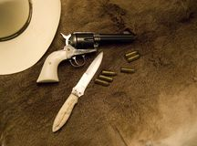 Old Western Weapons. Showing a hat, a gun, bullets and a knife on top of an old deer skin royalty free stock photos