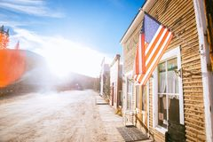 Old Western Wooden Buildings with flag of the united states, in St. Elmo Gold Mine Ghost Town in Colorado, USA. Hidden in mountains royalty free stock photos