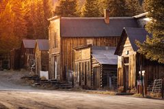 Old Western Wooden Buildings St. Elmo Gold Mine Ghost Town in Colorado, USA hidden in mountains. With yellow sun glow stock photos