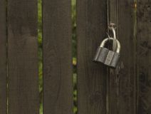 Padlock. Old wet padlock on old plank fence Royalty Free Stock Images