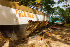 An old whaling boat named trouble at lower bay beach in the grenadines Stock Image