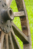 Old Wheel. Old wooden wheel standing with grass background (Selective Focus Stock Photo