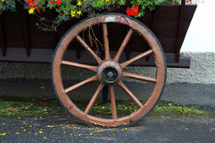 Old wheel. Of a cart with flovers Royalty Free Stock Photos