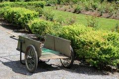 Old wheel barrel with rake near garden Stock Image