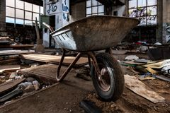 Old wheel barrow in abandoned industrial building royalty free stock image