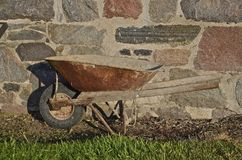 Old wheel barrow blends with foundation Royalty Free Stock Photo